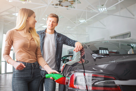Young smiling family couple buying first electric car in the showroom. Close-up of attractive woman charging ecological hybrid car with the power cable supply plugged in while watching at her husband. Eco-friendly auto concept.