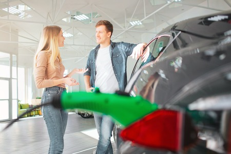 Young couple buying a first electric car in a showroom. Ecological vehicle concept. Modern technology in the automotive industry