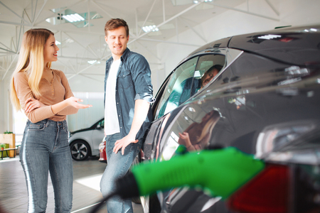 Young couple buying a first electric car in a showroom. Discussion about payment. Modern technology in the automotive industry Stock Photo