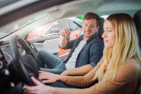 Young family buying first electric car in the showroom. Attractive man holding car key in the cabin of modern electric hybrid vehicle before test driving. Futuristic power. Electric car sale concept
