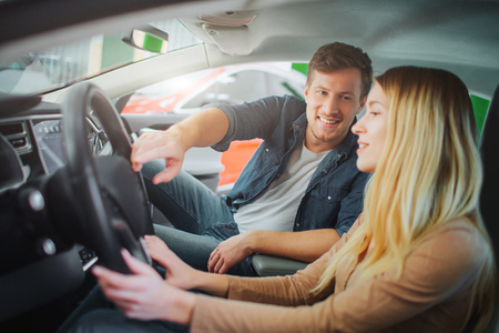 Young family buying first electric car in the showroom. Attractive smiling man showing buttons on steering wheel to his wife while they sitting in luxury eco-friendly vehicle. Electric car sale concept Stock Photo