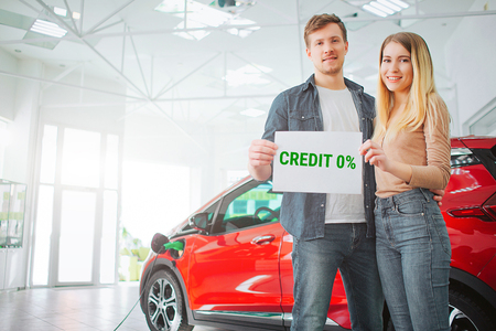 Young family buying first electric car in the showroom. Smiling attractive couple holding paper with word Credit while standing near eco red vehicle. Battery electric car for ecology Stockfoto