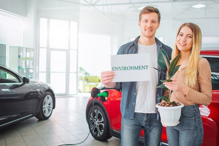 Young family buying first electric car in the showroom. Smiling attractive couple holding paper with word Environment and flowerpot while standing near eco red vehicle. Green car for environment