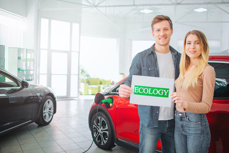 Young family buying first electric car in the showroom. Smiling attractive couple holding paper with green word Ecology while standing near electric vehicle. Eco-friendly car protects an ecology Stock Photo
