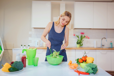 Vegan beautiful blonde woman cooking delicious salad in the kitchen. Vegetarian food. Healthy eating. Vegan diet Stock Photo - 120568265