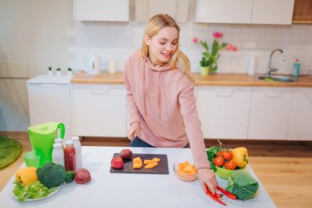 Vegan beautiful blonde woman cooking raw vegetables in the kitchen. Raw food diet. Vegetarian food. Healthy eating