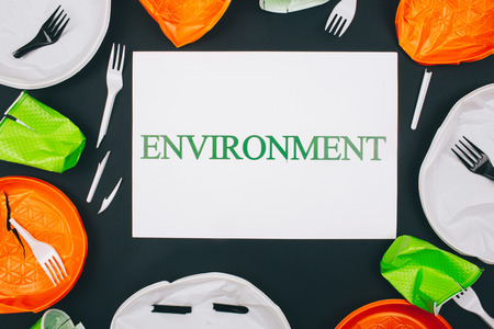 Plastic pollution and environment protection. Paper with word Environment in the centre of disposable broken plastic plates and forks on dark background. Single-use plastic, evironmental problem. European directive. Top view Фото со стока
