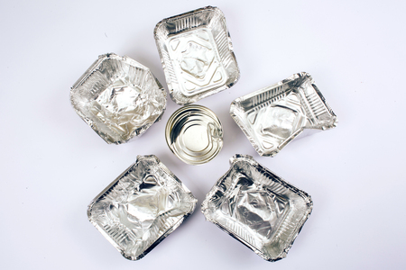 Plastic pollution concept. Metal can in the center of foil containers for food on white background, top view. Single-use plastic. New rules to reduce plastic waste, EU directive. We can no longer pollute our planet