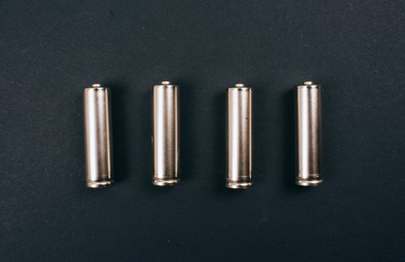 Recycling, reuse, reduce concept. Single-use silver batteries in the row on dark background, top view. Protect an environment. Single-use electric waste Stockfoto