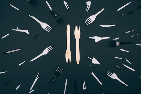 Plastic free. Zero waste concept. Eco-friendly unbroken forks in the center of single-use broken white and black forks on dark background. Choose single-use plastic or natural recyclable product. Top view Stock Photo