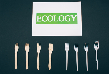 Be plastic free. Zero waste. Paper with word Ecology near eco-friendly natural and single-use forks in the row on dark background, top view. Single-use plastic or reusable recyclable product. Reduce reuse recycle