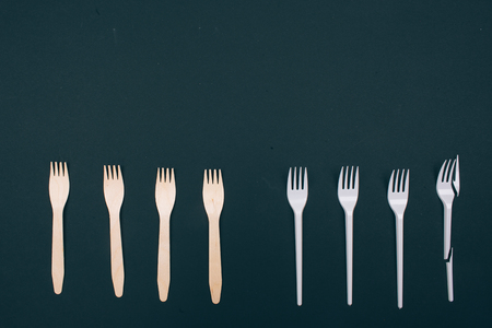 Be plastic free. Zero waste. Eco-friendly natural and single-use forks in the row on dark background, top view. Reduce reuse recycle. Single-use plastic or reusable recyclable product