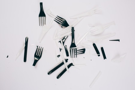 Plastic pollution concept. No to plastic. Broken single-use white and black forks on dark background. New rules to reduce plastic waste, EU directive. We can no longer pollute our planet. Top view