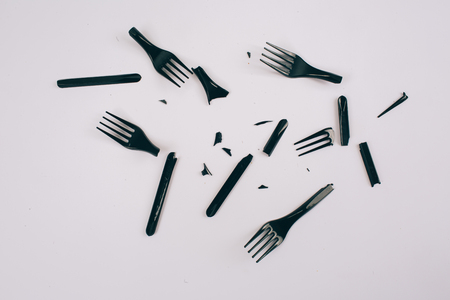 Plastic pollution concept. Plastic free. Broken single-use black forks on dark background, top view. New rules to reduce plastic waste, EU directive. We can no longer pollute our planet