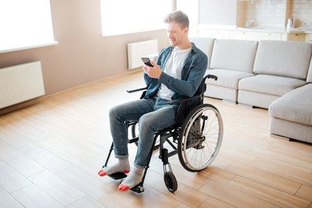 Nice young man with inclusion and disability. Sitting on wheelchair. Holding phone in hands and look at it. Daylight in big empty room. Stock Photo