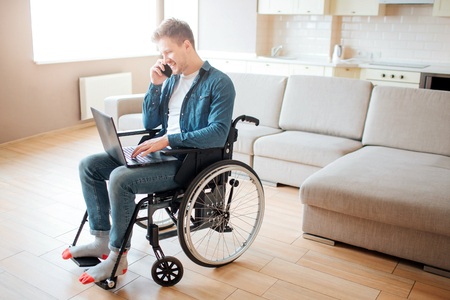 Young man with disability sitting on wheelchair. Working on laptop and talking on phone. Alone in big room with daylight.