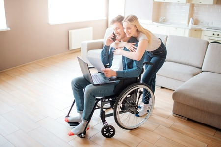 Young man with special needs. Sitting on wheelchair and talking on phone. Young woman embrace him. Standing from behind. Laptop on knees.
