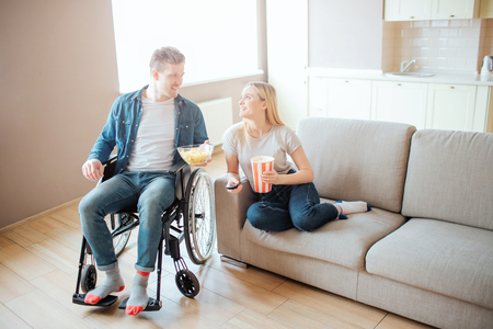 Young man with disability sitting beside woman on sofa. They look at each other and sile. Watching movie. Home cinema. Love. 版權商用圖片