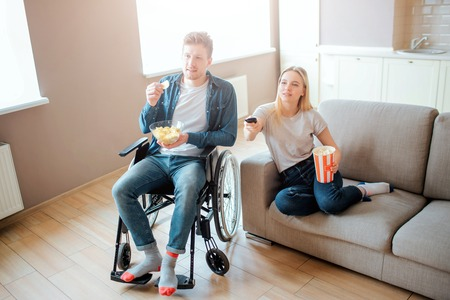 Young man sitting on wheelchair and watching movie with girlfriend. Guy with disability and special needs. Young woman sit on sofa and hold bowl with food. Remote control.