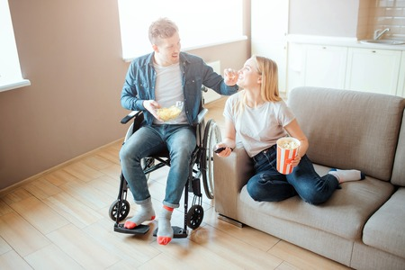 Young man on wheelchair sitting beside woman on sofa. Person with disability and special needs. Watching movie. Holding bown with chips and popcorn can.