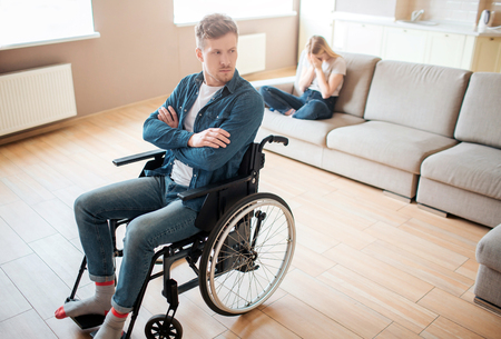 Young man with inclusiveness and disability sit on wheelchair in front. Hands crossed and upset. Young woman sit behind on sofa and cry. Emotional sickness and stress.