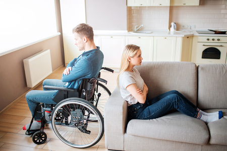 Young man with special needs and healthy woman sit back to back in room. Argue and quirrel. Worker with disability and inclusiveness. Upset and unhappy couple.