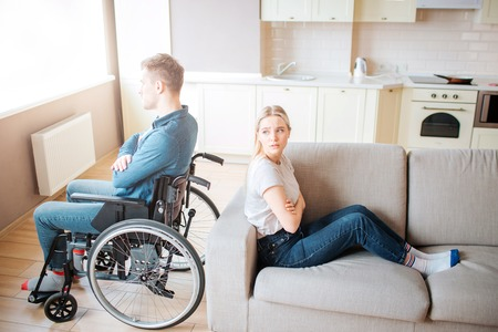 Young man with disability sit on wheelchair and look at window. Argue and quirrel. Guy with special needs sitting back to back with girlfriend. Young woman try to look at him. Stock Photo