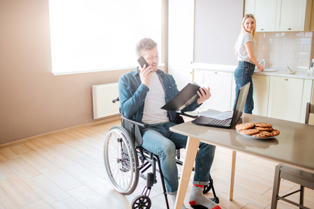 Busy young student on wheelchair studying and taking on phone. Guy with special needs and disability. Holding opened folder. Young woman stand at stove and cooking. Look back at guy.