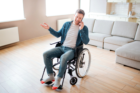 Young person with inclusion and disability. Sitting on wheelchair and talking on phone. Busy young man. Alone in empty room. Casual look.