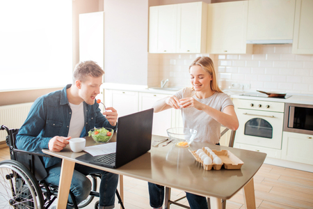 Young man with inclusiveness and special needs eating salad in kitchen. Sit on wheelchair and studying. Young woman sit besides and break eggs. Working together.