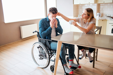 Sick young man with special needs and disability sneezing. Sick and ill guy. Young woman sit beside in kitchen and take care of him. Daylight.