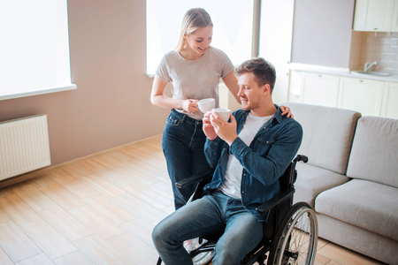 Young man with disability sit on wheelchair. Person with special needs. Holding cup of coffee together with girlfriend. She stand besides and hold hand on his shoulder.