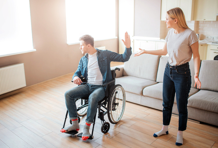Young man on wheelchair argue with girlfriend. Disability and inclusiveness. Person with special needs. Upset and unhappy young woman. 版權商用圖片