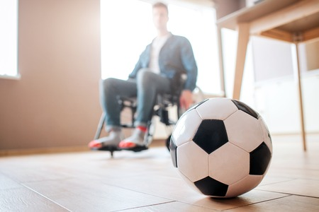 Young man with disability sitting on wheelchair and look down at ball for game. Ex sportsman. Upset and unhappy. Trauma. Cant play football anymore. Stock Photo