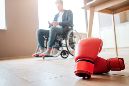 Upset young ex-sportsman with disability and inclusiveness sitting on wheelchair. Boxers gloves lying on floor. Cant use them anymore. Person with special needs.