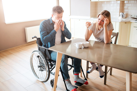 Sick young man with inclusiveness sneezing with healthy woman at table. Sick people in kitchen. Headache and pain. Person with special needs.
