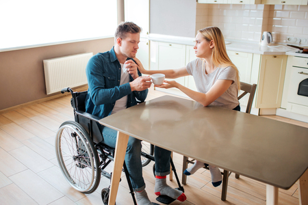 Young woman take care of man with special needs. He sit on wheelchair and get cup of hot drink. Sick and ill. Man with disability and inclusiveness.