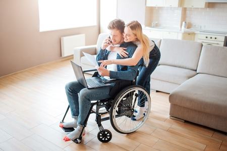 Student with disability sitting on wheelchair. Cheerful woman stand behind and embrace him. Looking on laptop. Young man with special needs. Couple together.