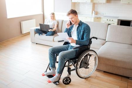 Trabajador joven con discapacidad en habitación. Sosteniendo un trozo de papel y hablando por teléfono. La mujer joven se sienta detrás en el sofá con el ordenador portátil. Luz. Pareja. Foto de archivo