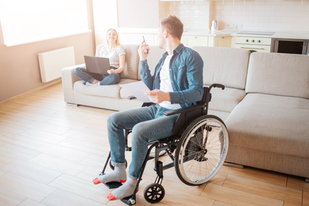Cheerful couple in room together. Young man with inclusiveness sit on wheelchair and look back on woman. Holding phone in hands nad laptop on knees. Smile to each other.