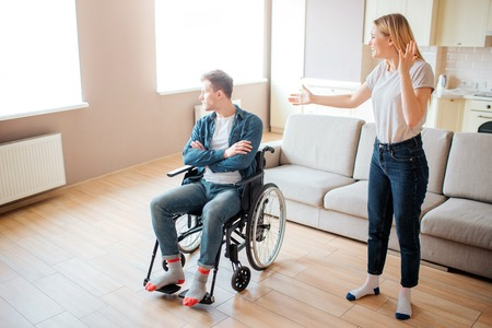 Upset young man on wheelchair look on window. Guy with special needs and disability. Young woman stand beside and argue with him. Stress and emotional sickness. 版權商用圖片