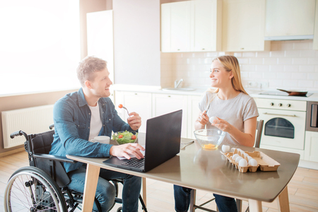 Happy cheerful young student with disability and inclusiveness eating salad and studying. He look at woman and smile. She cooks. Happy couple sit together in kitchen.
