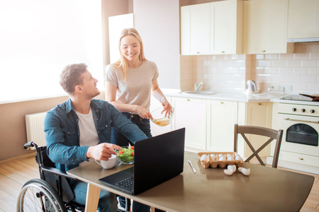 Young worker sit on wheelchair and look at woman. He work with laptop and eat salad. They look at each other and smile. Woman stand beside guy. Happy couple together. Stock Photo