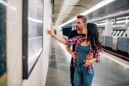 Young man and woman use underground. Couple in subway. Casual people in metropolitan. Young woman point on wall and smile. Guy hold hands on her hips. 版權商用圖片