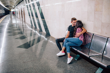 Young man and woman use underground. Couple in subway. Lovely young man and woman sit together. He embrace her and kiss. Love at first sight. Urban view. 版權商用圖片 - 121640058