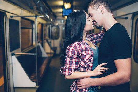 Young man and woman use underground. Couple in subway. Romantic kiss. Alone together in carriage. Tender picture. Standing in middle of subway carriage.