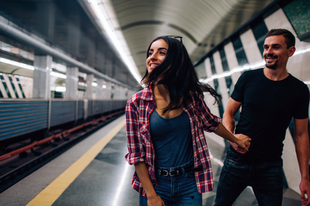 Young man and woman use underground. Couple in subway. Cheerful picture of young woman with man. He hold her hand and follow model. Love story. Underground action. 版權商用圖片 - 121640238