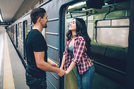 Young man and woman use underground. Couple in subway. Young brunette stand in underground carriage and smile. She hold mans hands. Guy stand on platform. Love stiry. Cheerful. 版權商用圖片 - 121641283