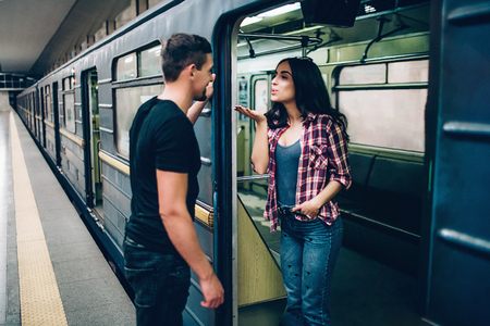Young man and woman use underground. Couple in subway. Lovely young woman send kisses to man. Guy look at her and smile. Together alone on platform and underground carriage. 版權商用圖片