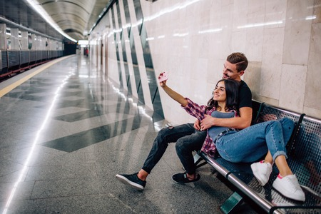 Young man and woman use underground. Couple in subway. Young woman taking selfie of herself and boyfriend at empty metro station. Smile and pose. Love story. 版權商用圖片 - 121641532